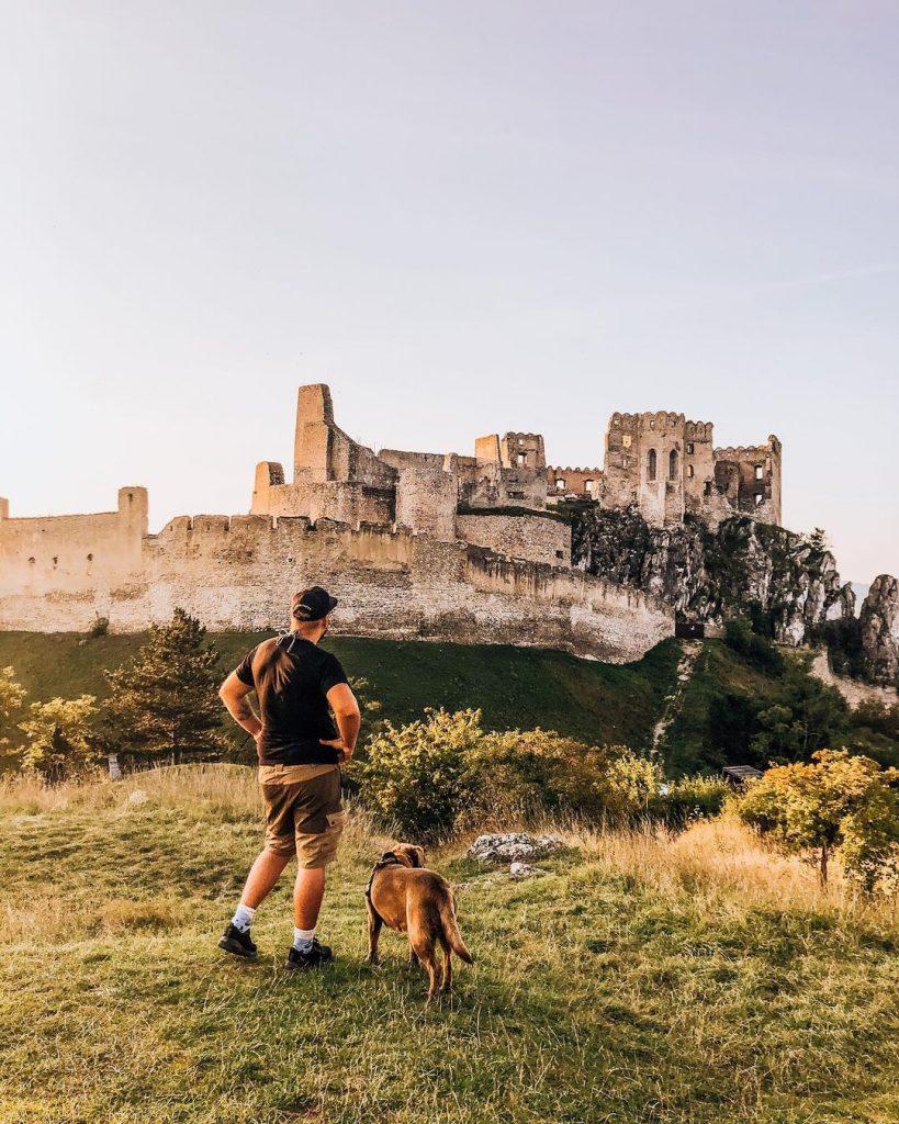 Hrad beckov na skale, muž so psom na lúke